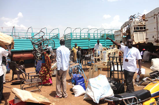 Mr. Tobias Lomuya (pointing at returnees offloading luggage) at the temporary campsite, Torit