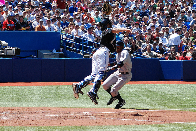 Yankees DH Curtis Granderson (right) gets ready to slide into home plate while Arencibia (left) desperately tries to catch the high throw from Aaron Hill