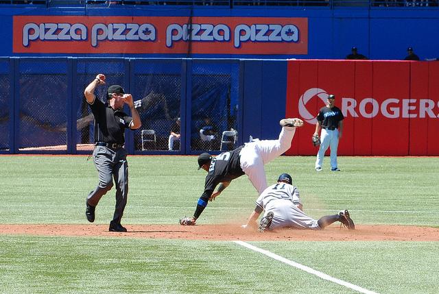 Yankee centre fielder Brett Gardner slides into second with a stolen base despite Yunel Escobar's acrobatic efforts