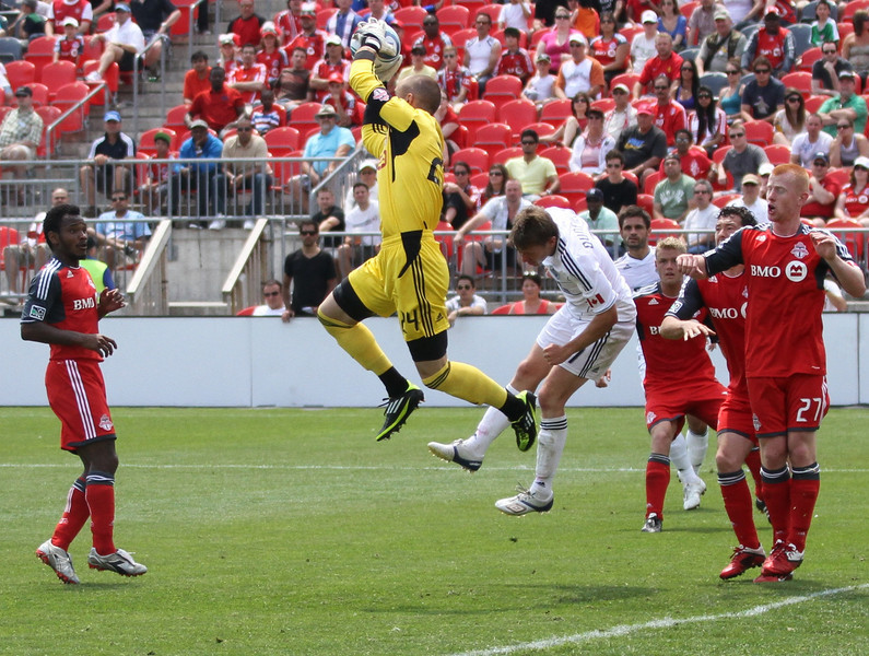 TFC goalkeeper Stefan Frei leaps above Whitecaps' Terry Dunfield to grab the ball in mid-air