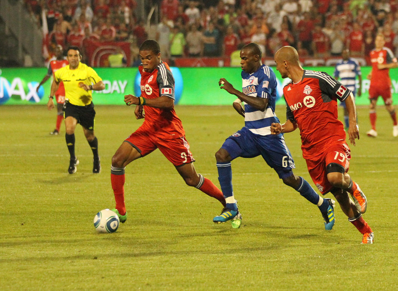 New TFC forward Ryan Johnson (left) pushes the ball past Dallas defender Jackson (centre) while Mikael Yourassowsky (right) looks on