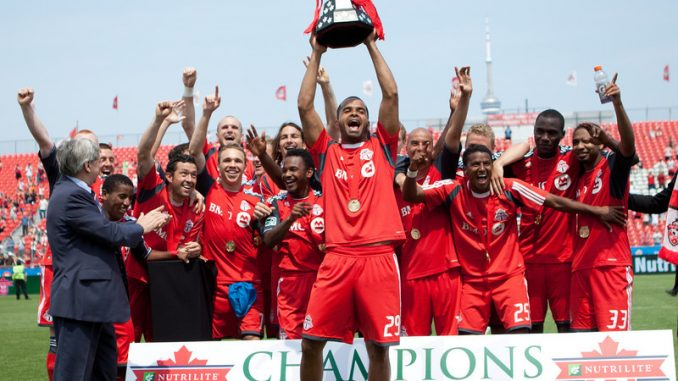 With his teammates behind him, TFC Captain Maicon Santos hoists the Voyageurs Cup in celebration of winning the NCC