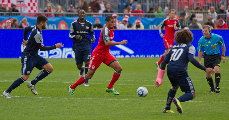 TFC forward Ryan Johnson (centre) finds an opening while being surrounded by Revolution players (JP Dhanoa)