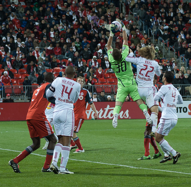 TFC goalkeeper Milos Kocic leaps up and outmuscles Red Bulls defender Stephen Keel to grab the ball out of the air (John Lucero)