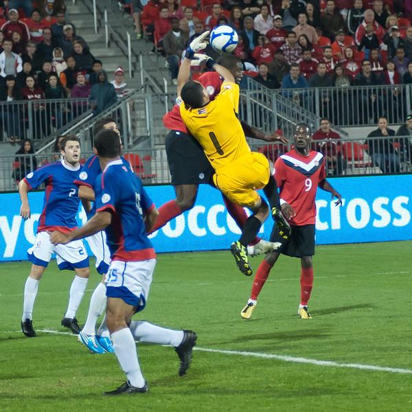 Canadian striker Olivier Occean goes up for a ball along with Puerto Rican goalkeeper Brandon Saldana (John Lucero)