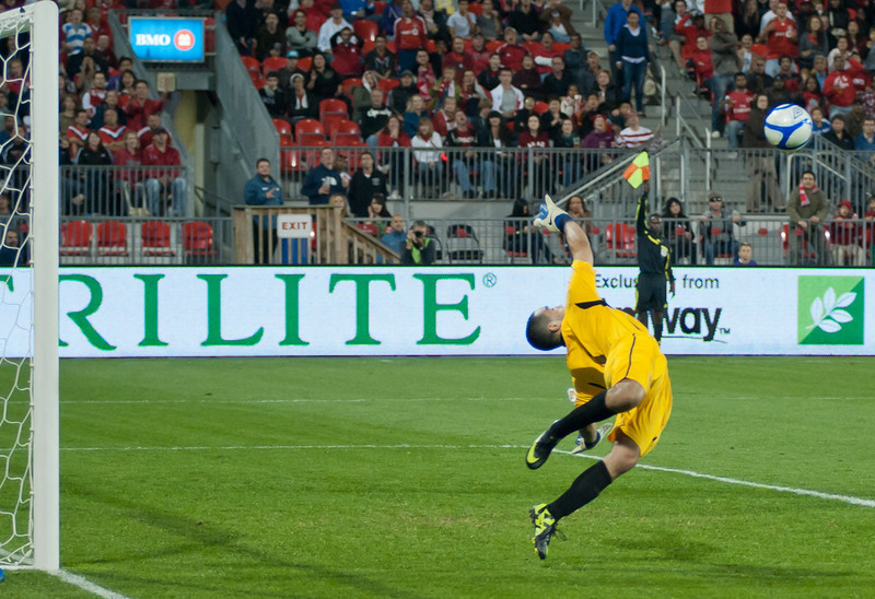 Puerto Rico's goalkeeper makes an acrobatic save on Tosaint Ricketts while the linesman raises his flag to signal offside (John Lucero)