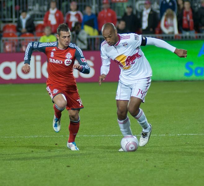 Henry keeps the ball away from Toronto FC forward Peri Marosevic (John Lucero)