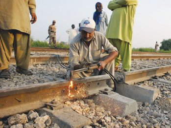 A man repairs destroyed railway track