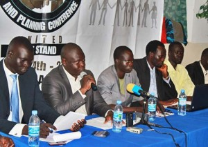 The chairperson of the convention organising committee Angok Akuien (holding microphone) briefs the press in Juba.[©Gurtong]