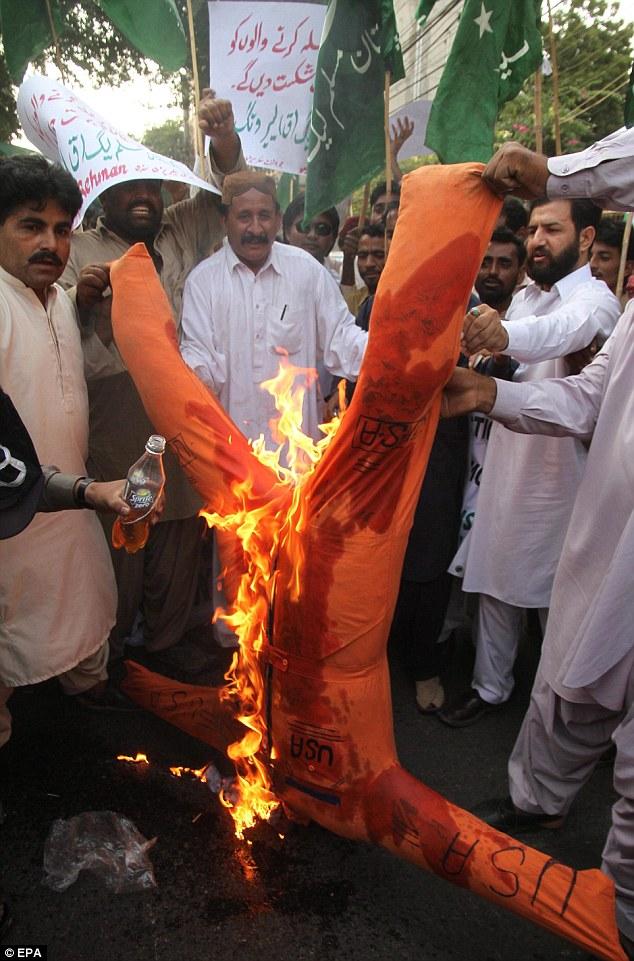 Angry demonstrators burn effigies of President Barack Obama