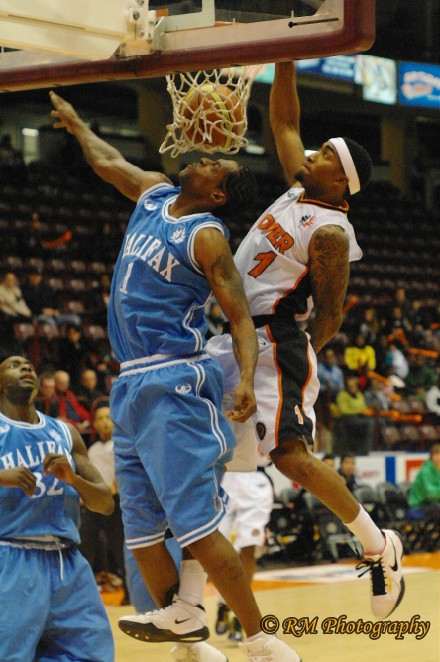Oshawa Power small forward Marcus Johnson wins the battle of number 1's as he slams the ball down onto the face of former NBA player Eddie Robinson of the Halifax Rainmen.