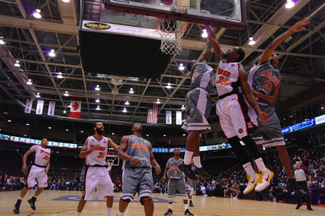 Oshawa Power small forward Akeem Wright muscles past a pair of Moncton Miracles for a dunk on Thursday night at the General Motors Centre