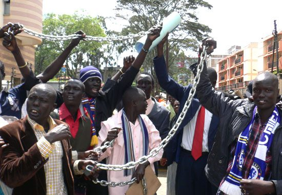 Angry students displaying the heavy metal chains they will use to close the embassy doors [©Gurtong]