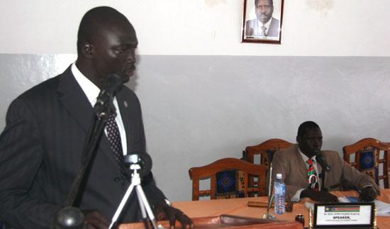 David Marial Gumke addressing parliamentarians as speaker John Marik (seated) listens [©Gurtong]