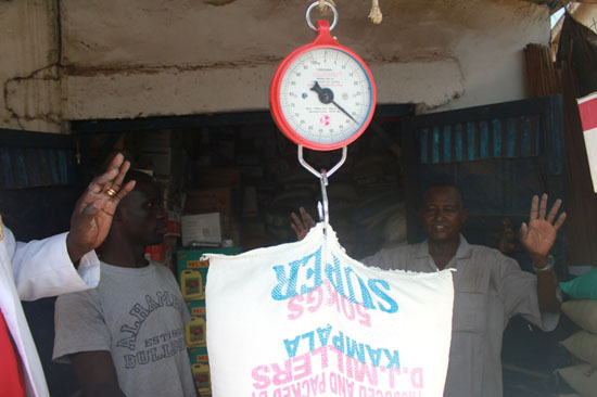 (L-R) Mr. Pangui and Rahma weighing a 50kg of flour during the random inspection by authorities in Juba [©Gurtong]