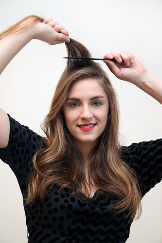 2. Leave a half-inch section of hair loose in the front, then use a comb to tease the remaining hair in the original triangle section. You want to create lift and volume at the roots.