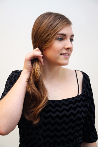 1. Start by creating a deep side-part and pulling all of your hair over to the opposite side, securing it into a low ponytail just below your ear.