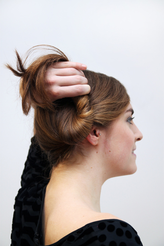 2. Twist the ponytail tail up and around to create a loose, low bun.