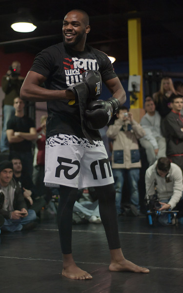 Jones shares a laugh while putting on a pair of boxing gloves before his open workout session in front of fans and media on Wednesday (John Lucero)