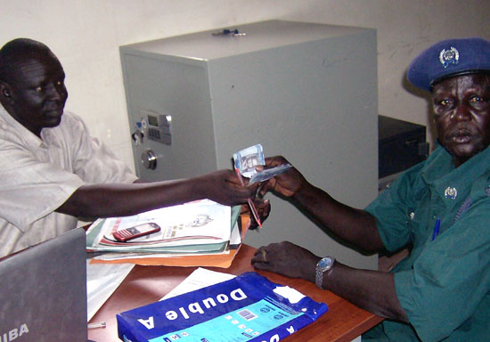 Controller of Accounts and Warrant officer Mr. John Tut Chol paying salary to a police officer in Bor town [©Gurtong]