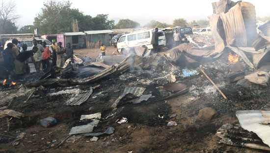 Affected traders sift through debris in the fire-ravaged Omoliha market in Torit [©Gurtong]
