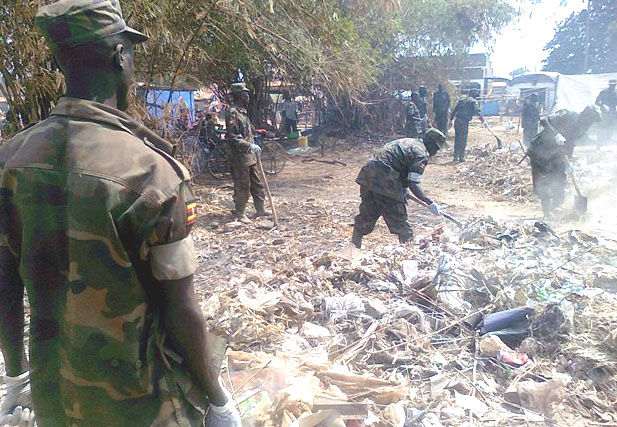Uganda People's Defence Force personnel cleaning Yambio market in commemoration of Army Week Day [©Gurtong]