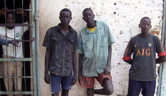 Mbini Brian Mbini (R) with the 2 suspects pose outside Bor police station holding cells [©Gurtong]