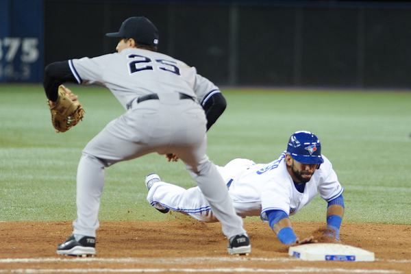 Toronto Blue Jays outfielder Jose Bautista slides into first base well before New York Yankees first baseman Mark Teixeira snares a ball thrown from catcher Russell Martin. Bautista homered in the game and now has five homeruns in seven games (Karan Vyas)