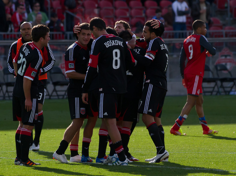 DC United Captain Dwayne De Rosario celebrates a 2-0 win with his teammates against his old team at BMO Field. In the background frustrated Toronto FC forward Ryan Johnson walks off the pitch (JP Dhanoa)
