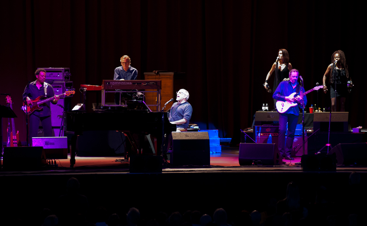 Donald Fagen playing the piano and behind him is Boz Scaggs with his guitar during a song set