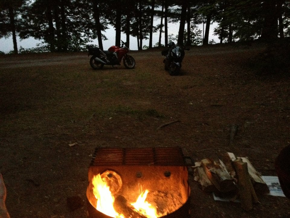 A lake view, a campfire and the trusty steeds: moto-camping at its best