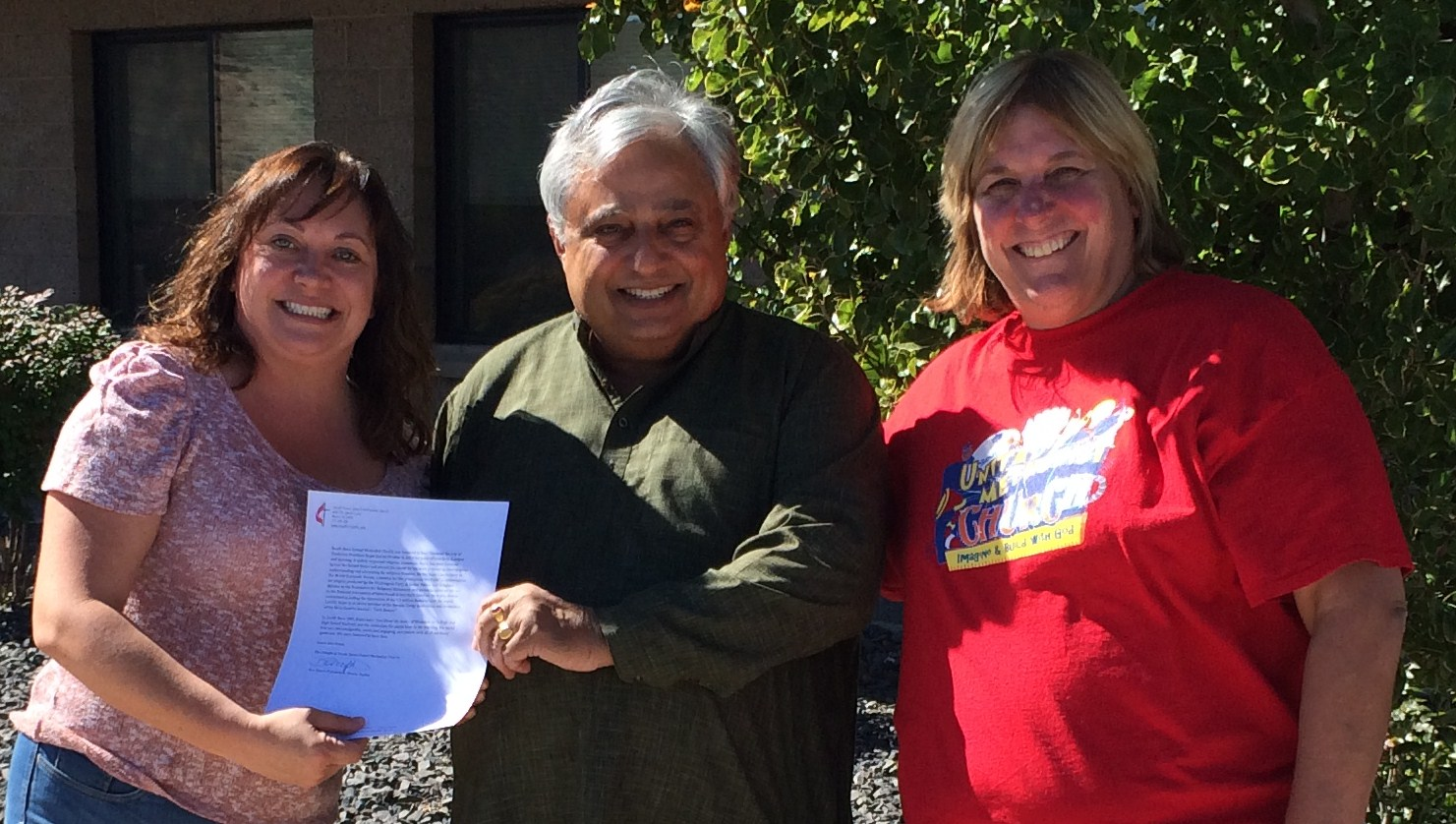 Rajan Zed receiving a testimonial at South Reno United Methodist Church. From left to right are—Dawn Pidlypchak, Rajan Zed and Pastor Becky Stockdale.