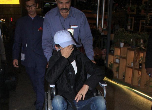 A wheelchair-bound Irrfan Khan hides his face as the paparazzi spots him at the airport