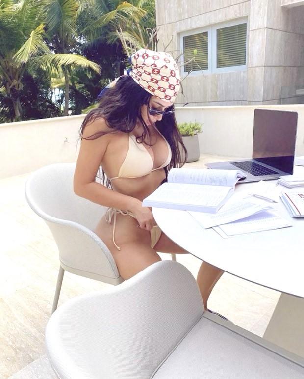 Kim Kardashian pairs her skimpy Skims bikini with Yeezy Foam Runner for a pool day